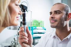 Optometrist examining female patient through ophthalmoscope Stock Photos
