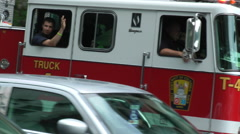 Fire Fighter waves, aerial truck passing Stock Footage