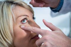 Optometrist putting drops into patients eyes Stock Photos