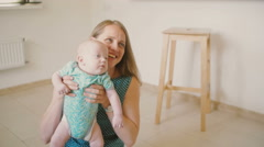 Young mother is lifting up her precious baby, talking to him with a smile while Stock Footage