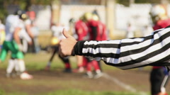 Referee making thumbs-up hand sign, defocused football players on scrimmage line Stock Footage