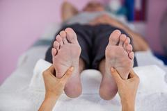 Senior man receiving foot massage from physiotherapist Stock Photos