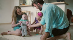 Young beautiful family is playing with the youngest baby son on the kitchen Stock Footage