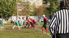 Referee watching offense and defense teams on scrimmage line, American football Stock Footage