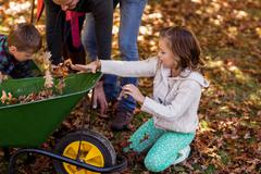 Children picking up autumn leaves with parents at park Stock Photos