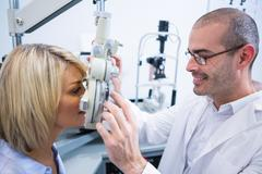Smiling optometrist examining female patient on phoropter Stock Photos