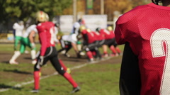 Anxious football player watching game, defocused rival teams fighting for ball Stock Footage