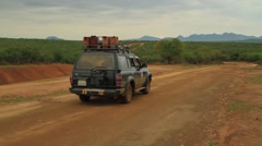 Beautiful Landscape With A Safari Type Vehicle Driving Down A Dirt Road Stock Footage