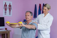 Senior man training with exercise band assisted by physiotherapist Stock Photos