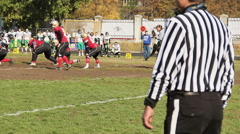 Referee supervising American football game, players taking positions before snap Stock Footage