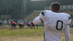 Tired American football player drinking water, having rest after intensive game Stock Footage