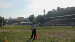 Field official showing thumbs-up to players and referees on gridiron during game Stock Footage