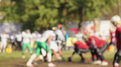 Defocused players of opposing football teams starting scrimmage to score points Stock Footage