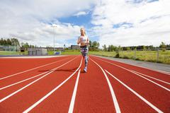 Fast athletic female runner on outdoor running track Stock Photos