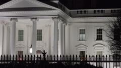 Pan White House night over fence Stock Footage