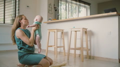 A beautiful young mother is holding up her adorable smiling baby helping him to Stock Footage