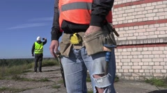 Construction worker try to find nails in to builders tool belt Stock Footage