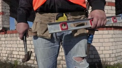 Construction worker put hammer in to builders tool belt Stock Footage