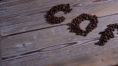 """The inscription """"coffee"""" on wood table, falling coffee beans. Slow-motion Stock Footage"""