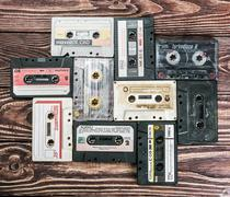Old Cassette tapes over textured wooden table Stock Photos