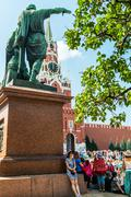 Kremlin clock chimes can be seen through the monument to Minin Stock Photos