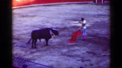 1948: Classic torero bullfighter red cape needs help against angry bull animal. Stock Footage