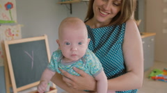 A face of a baby with blue eyes who is looking at the camera while his mother is Stock Footage