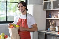 Handsome guy with packet of vegetables Stock Photos