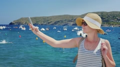 Woman in hat and sunglasses on the background makes selfie bay with yachts. In Stock Footage