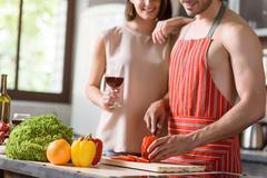 Joyful loving couple preparing healthy food - stock photo