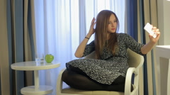 Female make selfy photo and send it using smartphone seating in hotel room Stock Footage