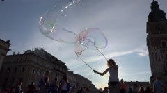 Man making very big soap bubbles on crowded square - blue sky, sun back light Stock Footage