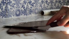 Tempering smooth dark chocolate on marble counter top surface Stock Footage