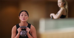 Asian woman doing a kettlebell workout at the gym Stock Footage