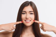 Happy woman pointing finger at her toothy smile Stock Photos