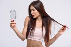 Attractive woman looking at her appearance Stock Photos