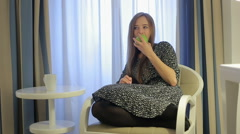 Pretty girl bite off apple seating in armchair Stock Footage
