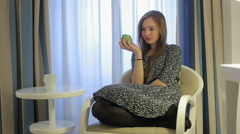 Lost in thoughts with tasty apple female bite off apple seating in armchair Stock Footage