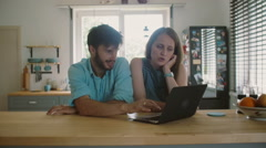 Young good-looking couple is sitting at the kitchen table looking at the Stock Footage