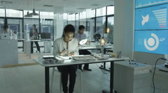 4K Timelapse research engineers working in lab building electronics & robotics.  Stock Footage
