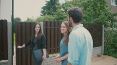 At the gates young couple is talking to businesslike brunette who shows them a Stock Footage