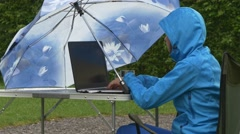 Business lady in waterproof clothing works on laptop at picnic table under rain Stock Footage