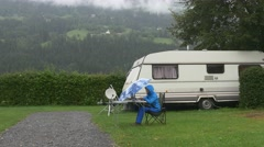 A woman works on laptop under blue umbrella under rain in camping near trailer Stock Footage