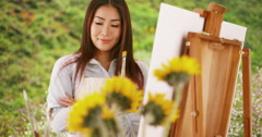 Japanese woman artist painting in the countryside Stock Footage