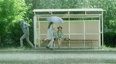Girl sitting at the bus stop in the rain. People in the rain with umbrellas. Stock Footage
