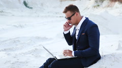 Businessman in the desert is working with a laptop and talking on a cell phone Stock Footage