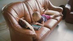 Acute blond little girl wearing all pink is lying on the sofa and playing a game Stock Footage