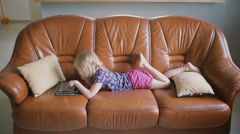 A side view of a cute blond little girl wearing all pink is lying on the sofa Stock Footage