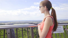 Woman on tall building observing nature push-out camera 4K Stock Footage