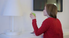 Girl in red eating an apple at working table Stock Footage
